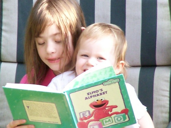 reading to little sister, caught in the act of reading, http://PragmaticMom.com