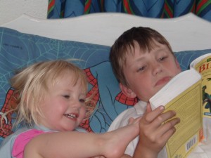 big brother conor reading to little sister layla, caught in the act of reading, http://PragmaticMom.com, pragmatic mom
