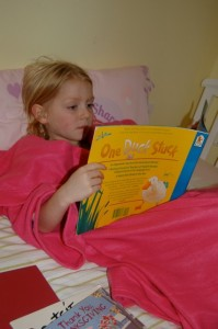 caught in the act of reading, http://Pragmaticmom.com, girls sisters reading in snugglies