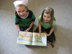 Fourth grader Eva J and first grader Julia C read A Place for Birds, caught in the act of reading, http://PragmaticMom.com