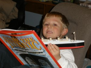 Kevin reading about and holding Titantic, caught in the act ... of Reading, http://PragmaticMom.com, PragmaticMom
