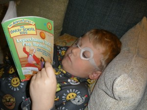 Kevin reading with homemade glasses, caught in the act of reading, pragmatic mom