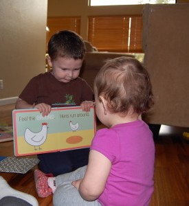 Turkeybird reading to littlebug, 1st daughter, There's a book, http://PragmaticMom.com, caught in the act of reading, pragmatic mom