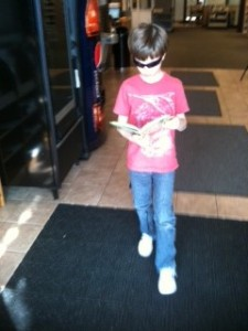 Caught in the Act of Reading Pragmatic Mom PragmaticMom walking and reading with cool sunglasses on