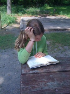 Caught in the act of Reading Pragmatic Mom Erica Perl girl reading at picnic table outside