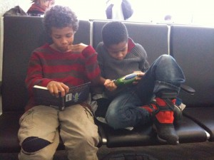 Caught in the Act of Reading African American boys reading at airport PragmaticMom PragmaticMom