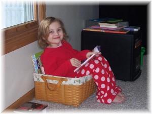 Tori caught in the act of reading pragmatic mom pragmaticmom child reading in reading basket cute girl