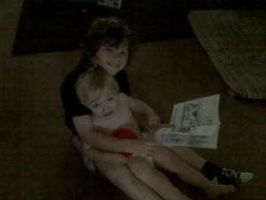 girl reading with toddler in her lap