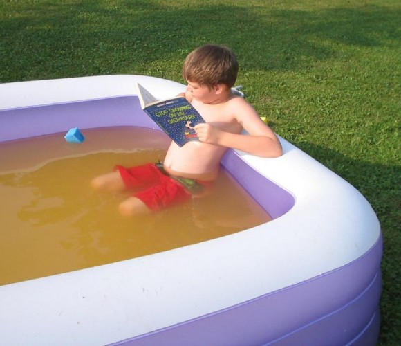 boy reading in pool
