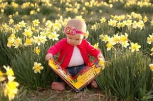 little girl reading in a meadow