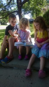 toddler reading to siblings