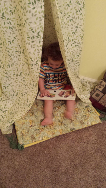 kid reading in tent