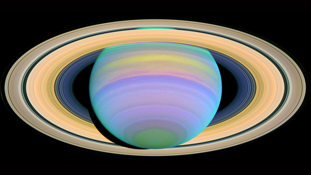 Saturn is seen here in ultraviolet light. Particles in Saturn's atmosphere reflect different wavelengths of light in discrete ways, causing some bands of gas in the atmosphere to stand out vividly in an image, while other areas will be very dark or dull.